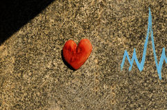 Wooden heart on the wall. And electro cardiograma symbol painted in blue Stock Photo