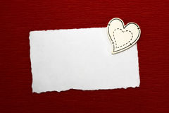Wooden heart and white sheet of paper. On a red background Royalty Free Stock Photo