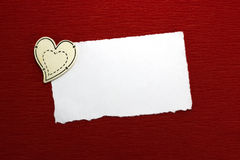 Wooden heart and white sheet of paper. On a red background Stock Photo