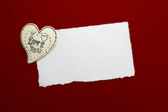 Wooden heart and white sheet of paper. On a red background Stock Photography