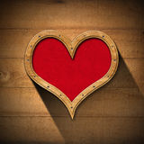 Wooden Heart on Wood Wall. Wooden porthole heart shape with red velvet interior, on wooden wall Stock Images
