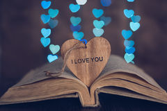 Wooden heart with the word love and background with a back of the heart. Beautiful background with bokeh Royalty Free Stock Images