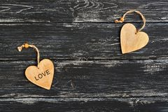 A wooden heart with the word love on a black wooden old background. Valentine`s Day.  Royalty Free Stock Photo
