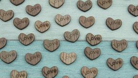 Wooden hearts on a background. Conceptual composition with wooden hearts with an inscription love stock footage