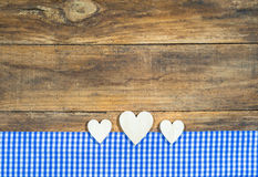 Wooden hearts border on blue and white checkered fabric. Background for Oktoberfest with hearts border, blue and white checkered fabric on rustic wood with copy stock photo