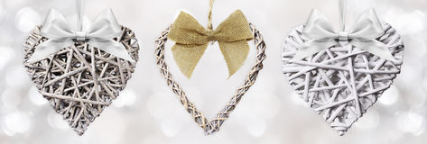 Wooden Hearts braided with ribbon bow isolated on silver blurred Royalty Free Stock Photography