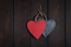 Wooden hearts on dark wood background Stock Photos