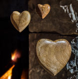 Wooden hearts floating against the fireplace. Wooden hearts floating against an old stone fireplace with fire burning Royalty Free Stock Photo