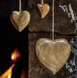 Wooden hearts. Hanging against an old stone fireplace Stock Images