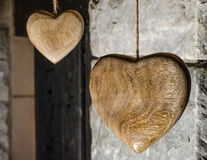 Wooden hearts. Hanging against an old stone wall Royalty Free Stock Image