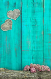 Wooden hearts hanging on antique teal blue fence with log and flowers border Royalty Free Stock Images