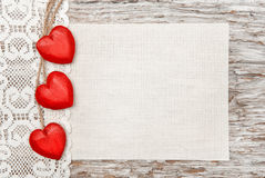 Wooden hearts, lacy cloth and canvas on old wood Stock Photos