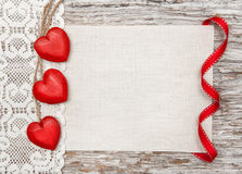 Wooden hearts, lacy cloth and canvas on old wood Royalty Free Stock Images