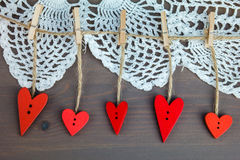 Wooden hearts on сlothespins on grey wooden background with lace. Stock Images