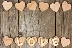 Wooden hearts and LOVE letters double border on rustic wood Stock Photography