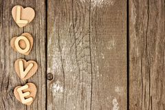 Wooden hearts and LOVE letters side border on rustic wood Royalty Free Stock Photos