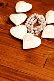 Wooden hearts lying on wooden table. Six wooden hearts lying on a wooden table surrounding a bracelet stock photo