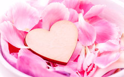 The wooden hearts on pink carnation petal. Stock Image