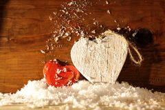 Wooden hearts in snow. Two wooden hearts in snow in front of wooden wall Stock Image
