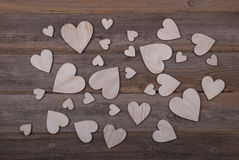 Wooden hearts on a wooden background. An image with different sized wooden hearts on a wooden background Stock Image