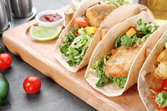 Wooden holder with yummy fish tacos. On kitchen table Royalty Free Stock Images