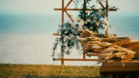 White flowers and soft green leaves adorn the wooden boards. Wooden holiday arch on the background of the sea, decorated with autumn flowers.nWhite flowers and stock footage