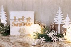 Wooden Christmas let it snow sign. Wooden holiday let it snow sign with Christmas trees ornaments and bright lights stock photography