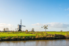 Wooden hollow post mill and a small metal polder mill next to ea Royalty Free Stock Photos