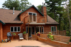 Wooden home. A wooden frame house with a large deck for entertainment and enjoyment sits in the wood of maine Stock Photo