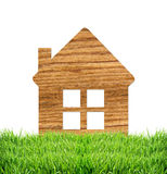 Wooden home icon on grass on white. Background stock images