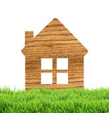 Wooden home icon on green grass, isolated on white Royalty Free Stock Photo