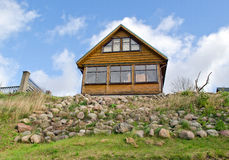 Wooden homestead house hill stone blue cloudy sky Stock Photo