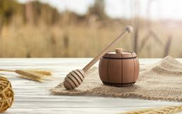 Wooden honey container and honey dipper on wooden table royalty free stock photography