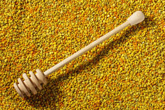 Wooden honey dipper on bee pollen granules surface Stock Photo