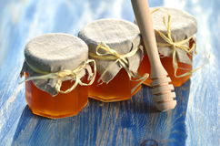 Wooden honey dipper and jars full of delicious fresh honey in apiary Royalty Free Stock Photos