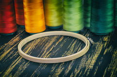 wooden hoop closeup on a background of colorful spools of thread Stock Photos