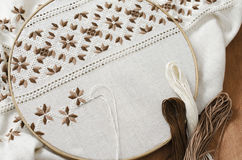 The wooden hoop with the embroidery pattern of brown and beige color on canvas, on wooden table.Rustic style. Selective focus. Royalty Free Stock Photos