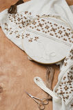 The wooden hoop with the embroidery pattern of brown and beige color on canvas, on wooden table.Rustic style. Selective focus. Stock Photo