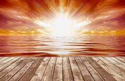 Tropical Sunrise. Wooden horizontal boardwalk in the foreground, and a fiery sun rising on the horizon on water in yellow white and orange flaming streaks Royalty Free Stock Photography