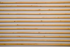 Wooden horizontal slats batten on a light gray wall background. Interior detail, texture, background. The concept of minimalism an royalty free stock images