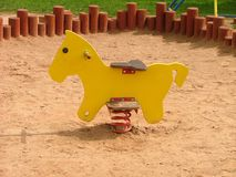 Wooden horse. Yellow playground's wooden horse Royalty Free Stock Images