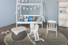 Wooden horse in a kids boy room interior.Stylish furniture in a monochromatic spacious kid`s room.Modern stylish child`s stock photos