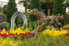 Wooden horse sculpture in the garden. Running horse sculpture between  beautiful flowers and trees Stock Photos