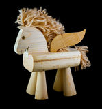 Wooden horse toy with wings on black background. Wooden self-walking horse toy with wings on black background Stock Photo