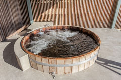 Wooden hot tub is filled with water on outdoor. Summer royalty free stock photography