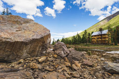 Wooden hotel in the mountains near a large rock Royalty Free Stock Photo