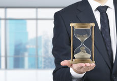 Wooden hour glass. Businessman holding sand glass on palm. Sand running, dollar sign down. Blurred office at background. Concept of time Stock Photo