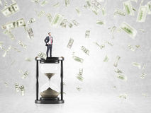 Wooden hour glass. Businessman standing on huge sand glass, dollars falling from above. Concept of time is money Stock Images