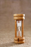 Wooden hourglass against a hessian background Stock Photos