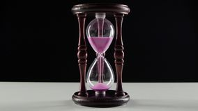 Wooden hourglass. Jet of sand in the hourglass. Black. Exquisite wooden clock is filled with pink sand, hourglass in wooden frame, pink sand pours in a thin stock footage